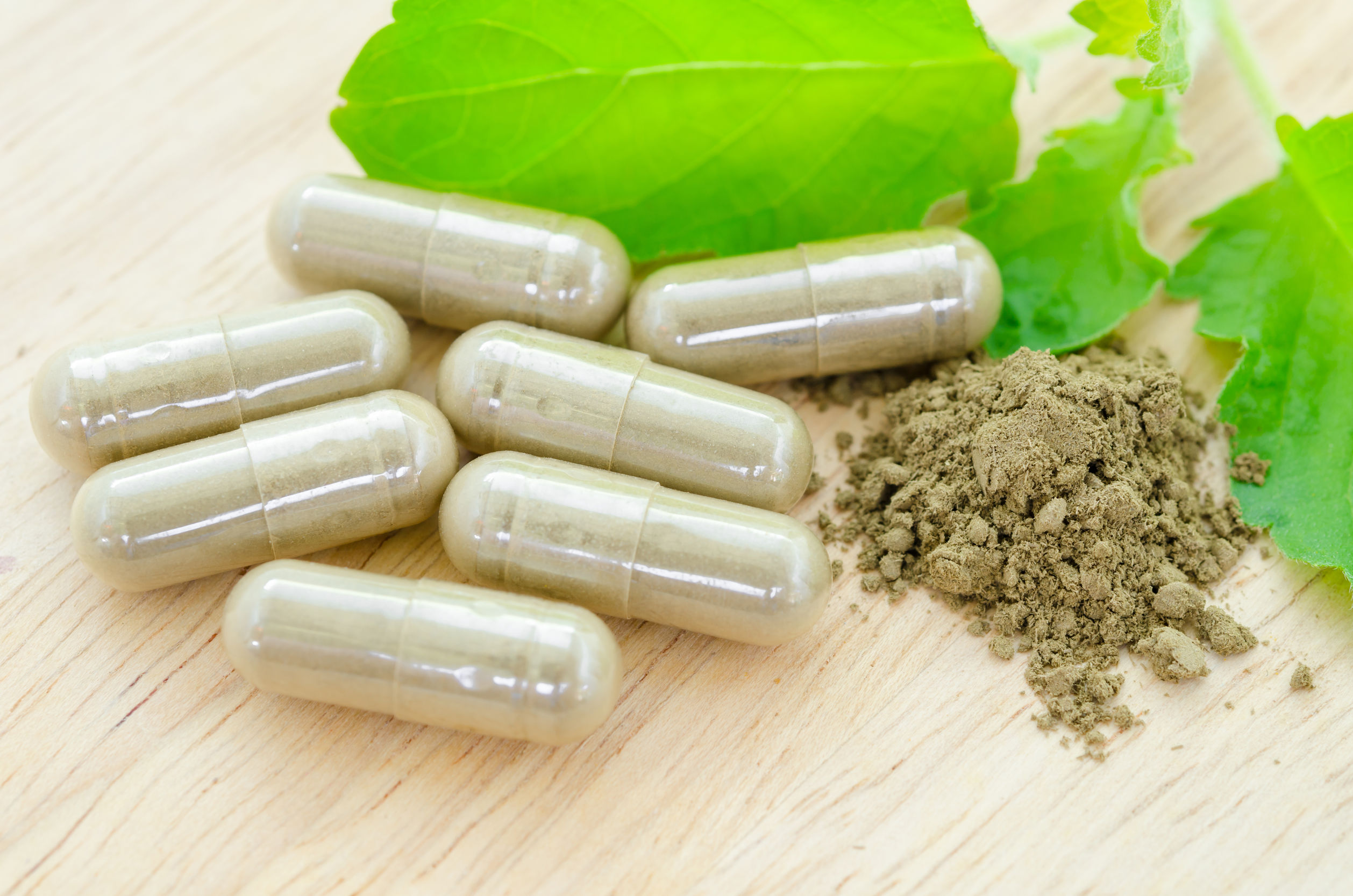 50243963 - herbal medicine capsules with green leaf on wooden background.